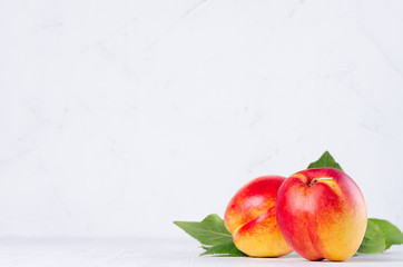 Juicy ripe whole nectarines peachs with young green leaves in soft light white wood board.