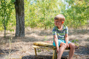 The boy sits on an old bench, in an abandoned park and looks around with a sad face.