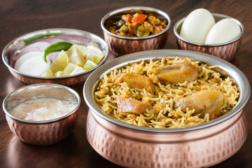 Chicken biryani with traditional sides - Closeup view from the top of delicious Indian chicken biryani served in authentic copper utensils with salad (raita), gravy and egg. Natural light used.