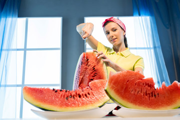 Young woman cuts watermelon with knife in the kitchen