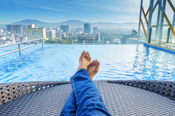 Male relaxing near swimming pool in hotel. Relaxing, Holiday & Travel concept.