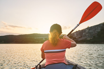 A red-haired young woman rowing on an inflatable kayak on a lake among beautiful mountains against the background of an orange sunset. Great disk of the rising sun. Sun rays. Sport