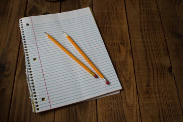 a notepad with pencils on wooden background