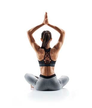 Young attractive girl practicing yoga isolated on white background. Concept of healthy life and natural balance between body and mental development. Full length