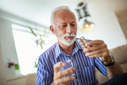 Senior man taking pills at home