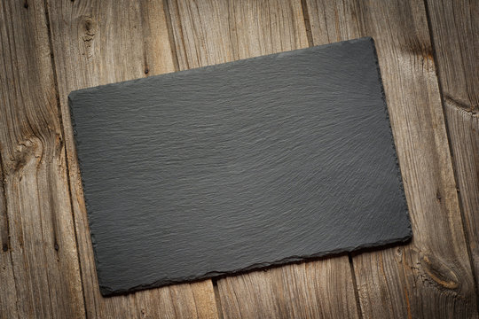 Slate blackboard on old wooden background. Flat lay.Top view.