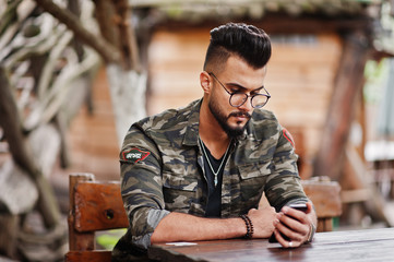 Awesome beautiful tall ararbian beard macho man in glasses and military jacket sitting outdoor wooden table of restaurant and looking his phone.