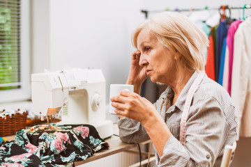 Adult woman is sewing in her studio. She is tired.