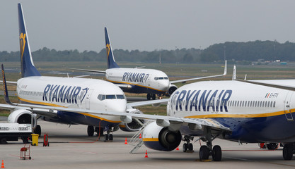 Ryanair airplane taxis past two parked aircraft at Weeze Airport