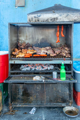 Meat and sausages in a barbecue for a parilladas (grilled meat) in a street of Uyuni, Bolivia