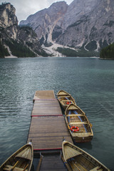 Breathtaking landscape scenic view of romantic, tourist popular alpine lake Lago Di Braies (Pragser Wildsee) in Dolomites mountains, Italy with iconic wooden boats on clear water.Lake activity concept