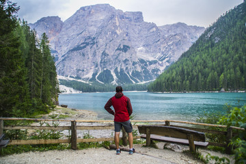 View of young tourist hiker man overlooking beautiful alpine lake Lago Di Braies (Pragser wildsee) in Trentino, Dolomites mountains, Italy. Tourist popular summer attraction/destination in Europe