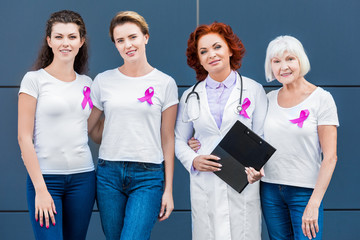 women and doctor with pink ribbons standing together and smiling at camera, breast cancer awareness concept