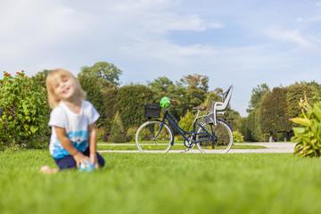 Kleines Kind spielt im Park mit Fahrrad im Hintergrund. Little child playing in park with retro biker in background.