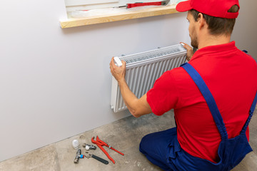 man installing heating radiator on the wall at home