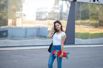A nice girl with a skateboard in her hands looks at the camera and smiles on a gray background. Modern leisure for teenagers. sport