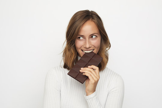 portrait of young woman biting in a pieace of chocolate looks Left