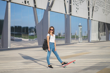 A teenage girl with a red penny board in her hands is standing, looking at the camera and smiling.