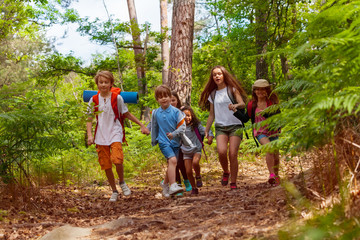 Group of kids running in the forest holding hands