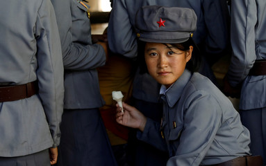 Soldier eats ice cream as she visits a zoo in Pyongyang