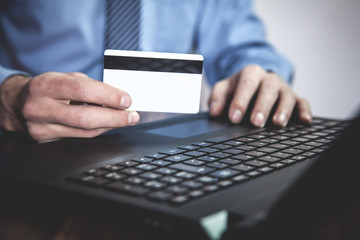 Man using laptop and showing credit card. Business concept