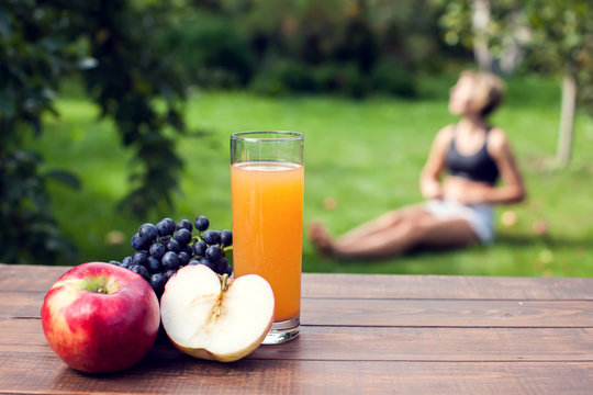 Lifestyle, sport and healthcare. A woman during yoga exercises outdoor. Healthy food on the table