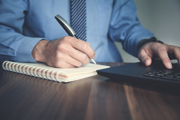 Businessman writing in notepad and using computer. Business concept