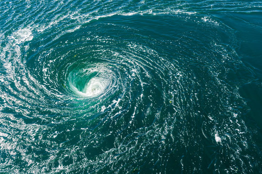 A powerful whirlpool is generated at the surface of the green waters of the river Rance by the action of a turbine of the tidal power station near Saint-Malo in Brittany, France.