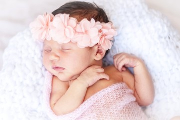 Cute sleeping newborn Caucasian baby girl a pink flower head bow. Sweet infant girl in her sleep. A classical newborn infant photo session. First days of her life concept