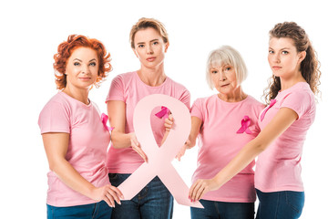 women in pink t-shirts holding breast cancer awareness ribbon and looking at camera isolated on white