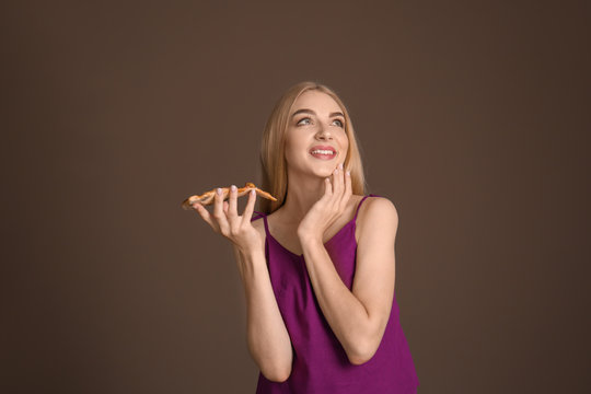Young woman eating slice of hot tasty pizza on color background