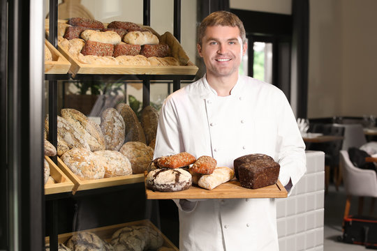 Man holding board with assortment of fresh bread in bakery
