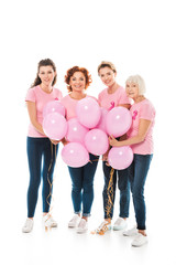 women with breast cancer awareness ribbons holding bunch of pink balloons and smiling at camera isolated on white