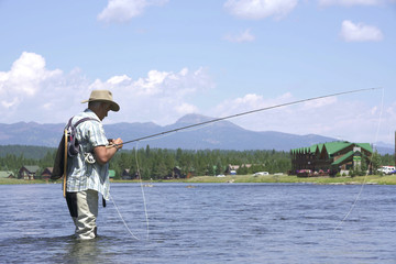 Fisherman putting fly on fishing line hook
