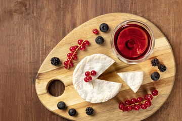 An overhead photo of Camembert cheese with a glass of red wine and fruits, on a dark rustic background with copy space
