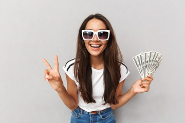 Photo of joyous woman with long dark hair in sunglasses showing peace sign and holding fan of dollar money, isolated over gray background in studio