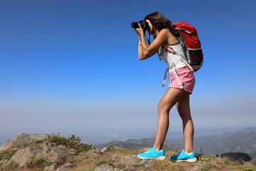 Young woman traveler taking photo on mountain peak