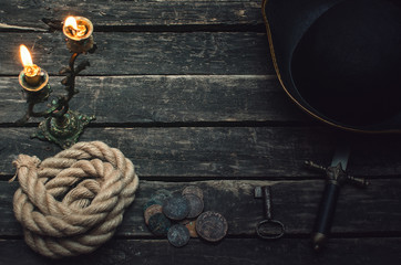 Pirate captain table with pirate hat, mooring rope, weapon, coins and burning candle. Treasure hunter concept.