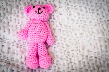 A soft pink teddy bear, toy for infant girl, isolated on a white blanket background. Sudden infant death syndrome stock image.