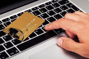 Closeup of a Man Typing on a Laptop with Credit Card