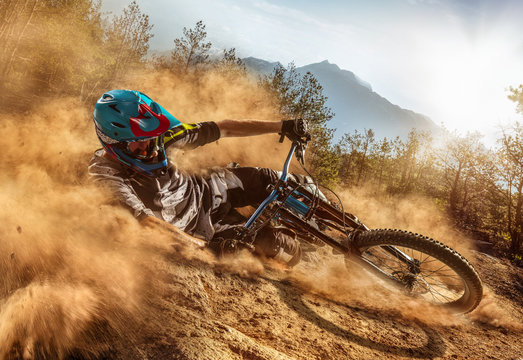 Mountain biker on forest trail. Male cyclist in dust rides the rock