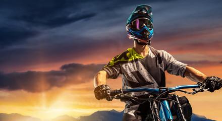 Mountain biker on sunset trail. Male cyclist portrait in sport helmet