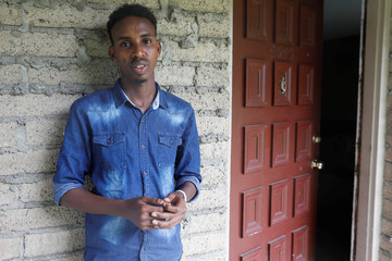 Aden Hussein Hassan poses outside his apartment in Columbus
