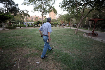 An Iraqi refugee and former interpreter for the U.S. Army in Iraq walks with his military hat in a garden on the outskirts of Cairo