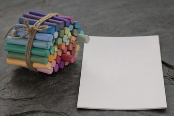 Pastel crayons and white watercolor paper on dark stone background. Copy space. Selective focus