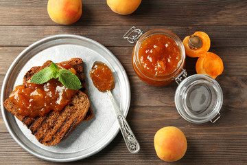 Toasted bread with delicious apricot jam on plate