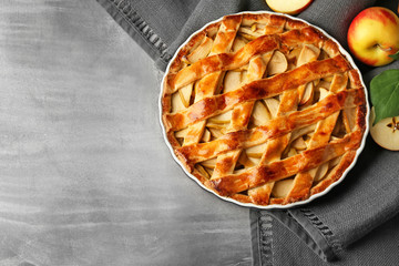 Dish with delicious apple pie on grey table