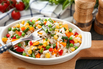 Dish with tasty boiled rice and vegetables on wooden board