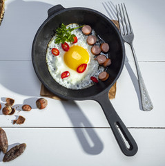 Aluminium Prints Egg black round frying pan with fried chicken egg and sausages