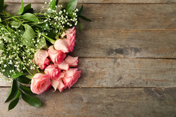 Bouquet of beautiful roses on wooden table